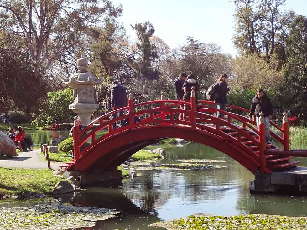 People walking over a red bridge in the Japanese Garden in Buenos Aires.