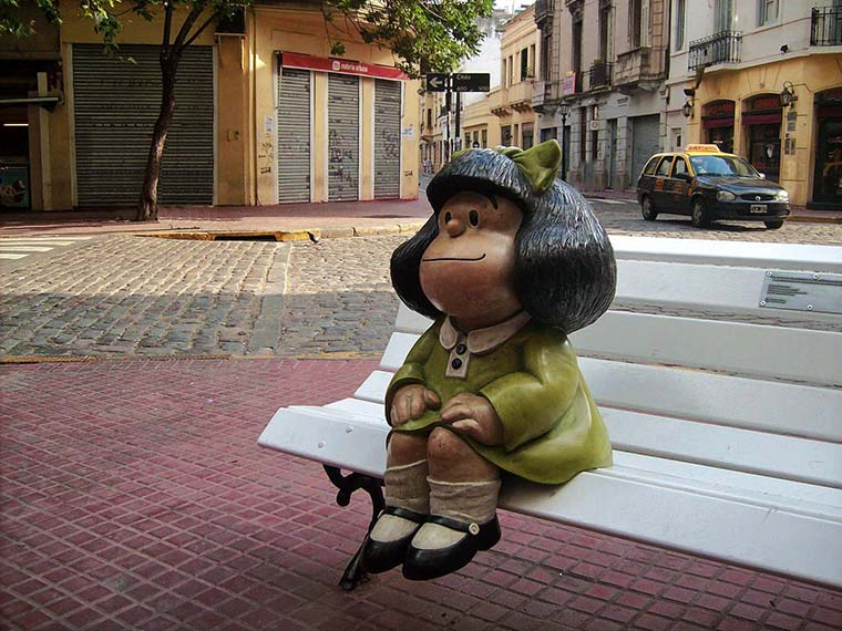 Mafalda statue sitting on a white bench in Buenos Aires.