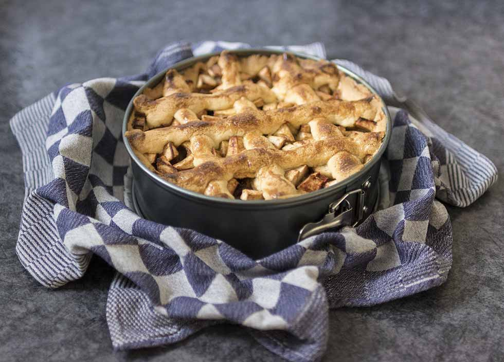 Typical Dutch Apple Pie in a black form and blue and white fabric