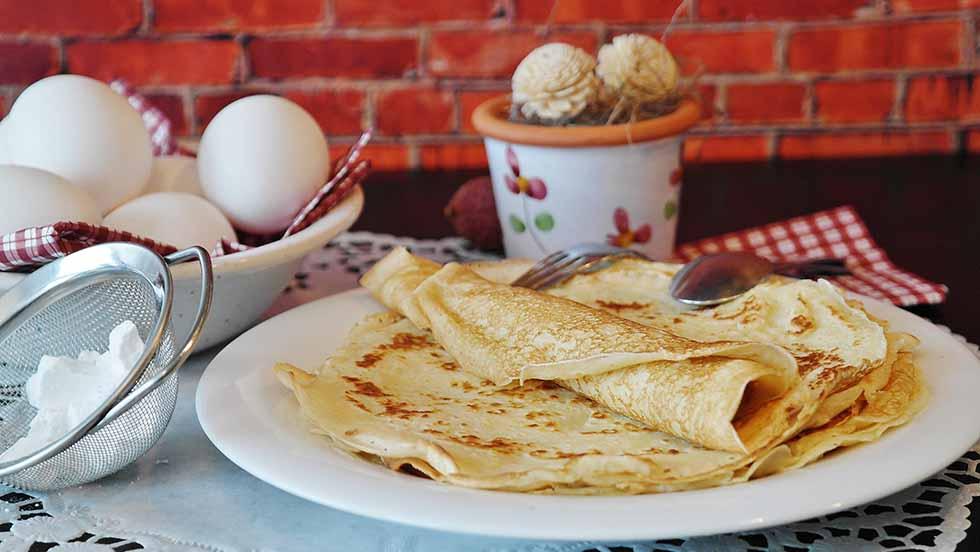 Typical Dutch food, a thin pancake on a white plate.