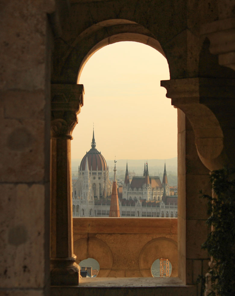 Hungarian parliament building seen from between columns in Budapest