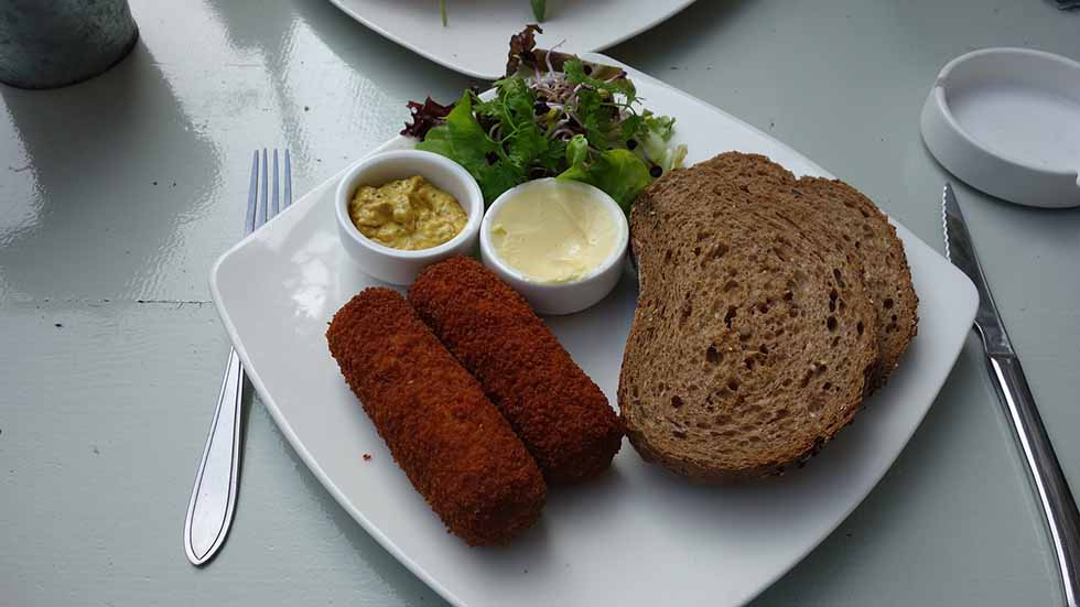 Dutch kroket with bread on a white board