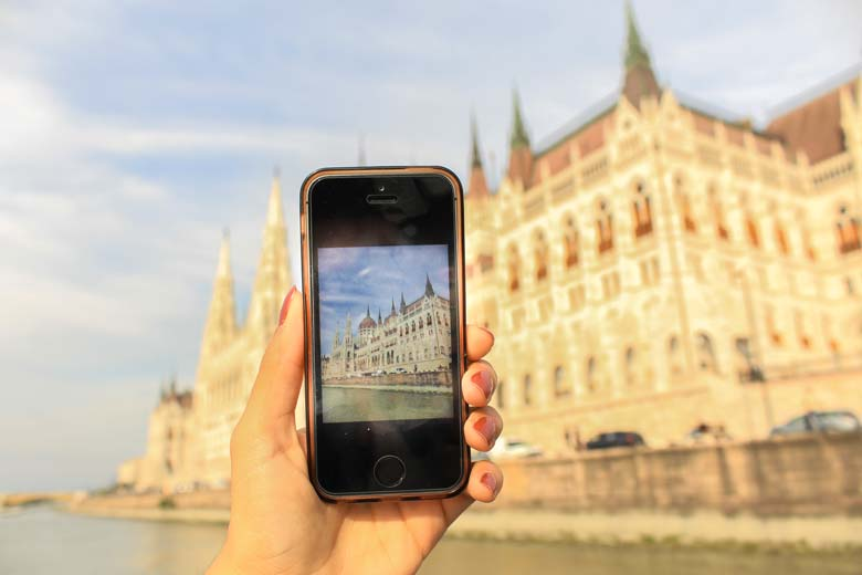 Hand holding Iphone with image of the Hungarian Parliament in front of the Hungarian Parliament