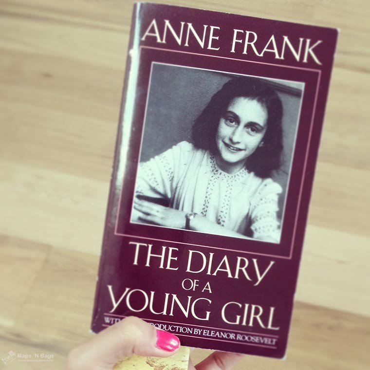 Hand of a girl wearing pink nail polish holding the purple book of Anne Frank in Amsterdam.