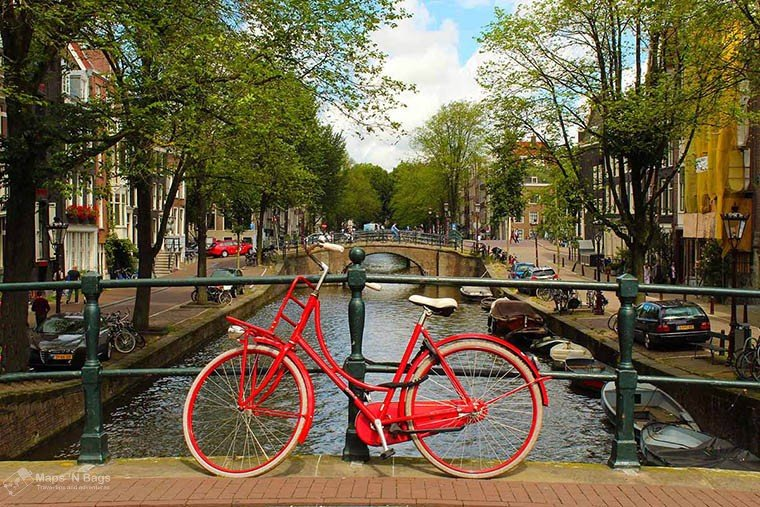 Red bike attached to a bridge over a canal in Amsterdam.