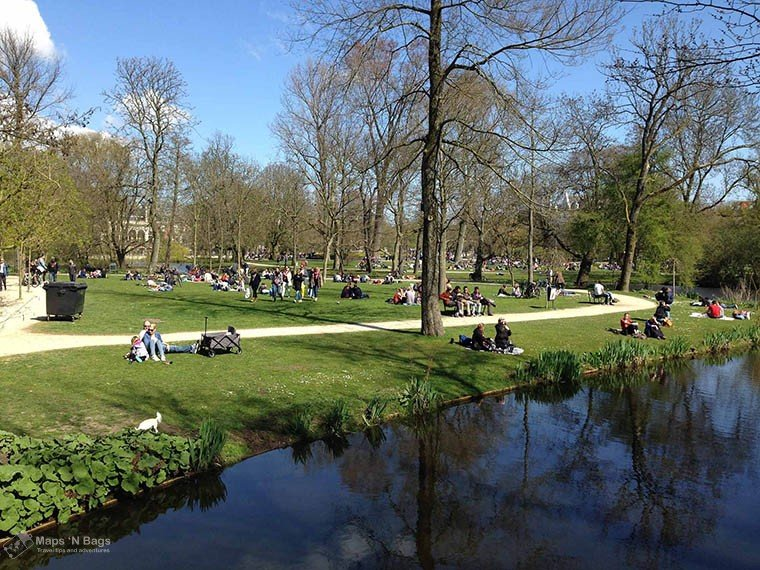 People chilling on the grass at the Vondelpark on a sunny day.