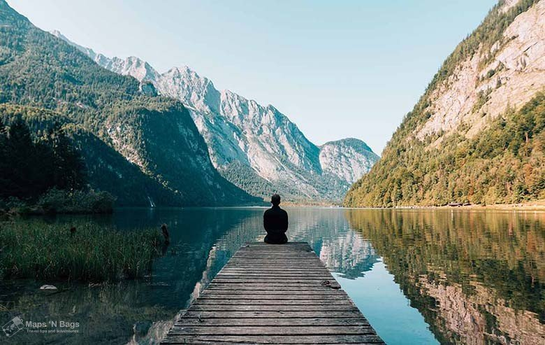header-man-sitting-wooden-path-water-mountains-reasons-love-to-travel