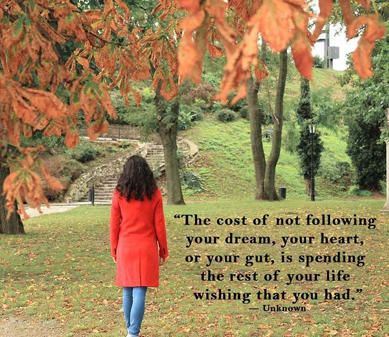 woman-dark-hair-red-coat-walking-grass-travel-quotes