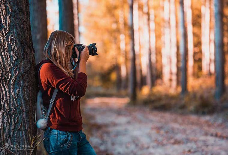 woman-red-sweater-photographing-forest-reasons-love-to-travel