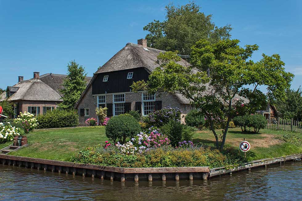 Cottage house with a green garden and colorful flowers by the water's edge in Giethoorn.
