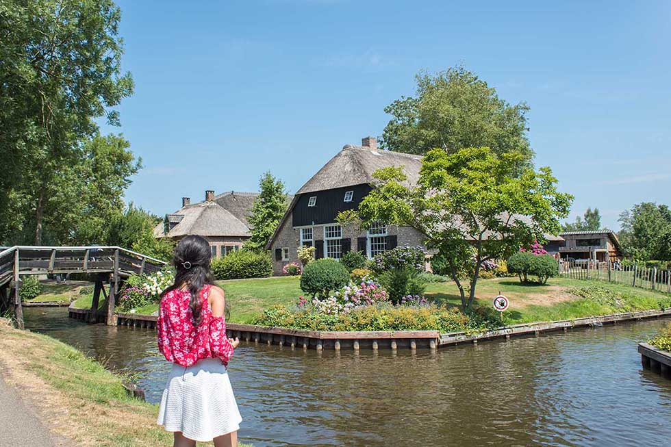 Woman wearing a red blouse standing by the water's edge and starring at a cottage house in Giethoorn.