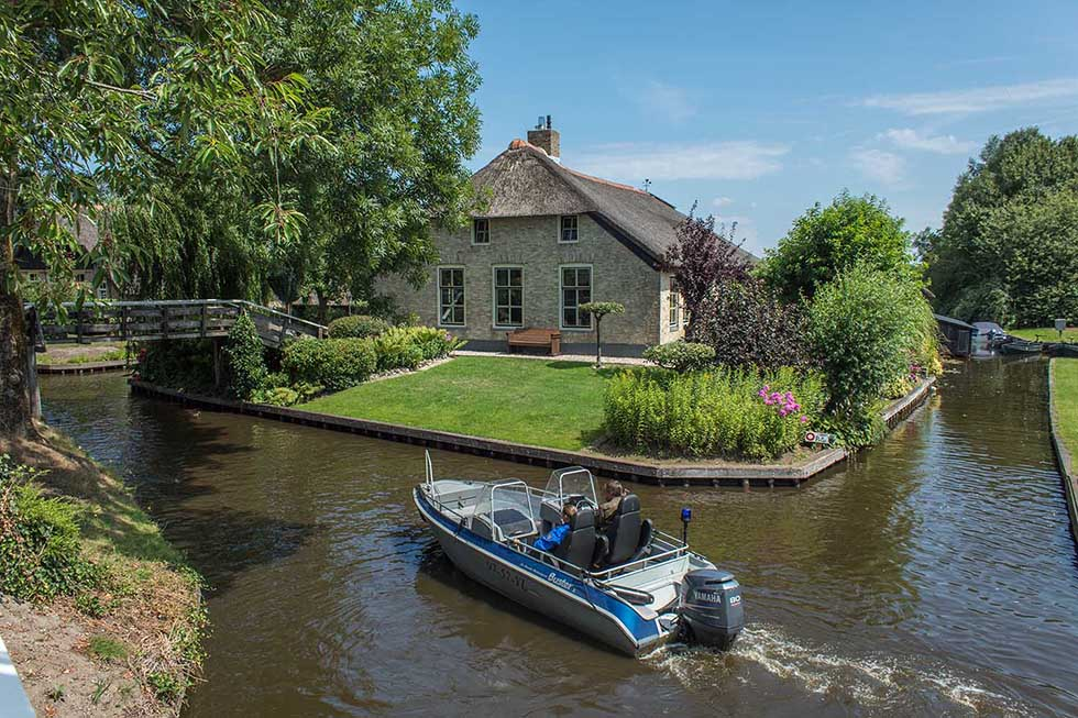 Police boat cruising in a canal in Giethoorn next to a cottage house.