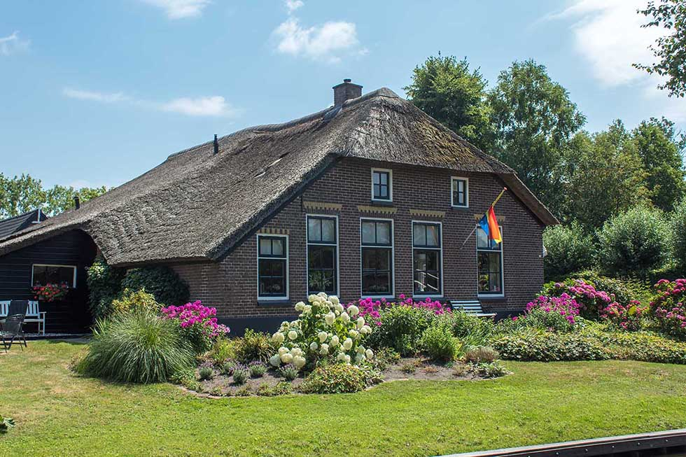 Cottage with green garden and colorful flowers in Giethoorn.