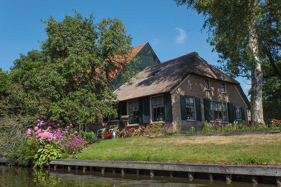 Cute cottage house and green garden on a sunny day in Giethoorn.