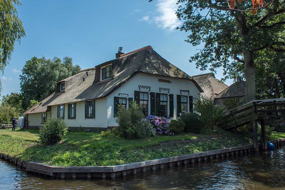 White cottage house and green garden in the fairytale village of Giethoorn.