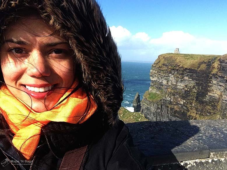 Girl wearing a hoodie and smiling at the camera at the Cliffs of Moher #Ireland #CliffsofMoher #Europe #Travel
