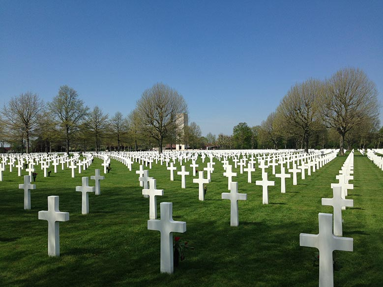 White crosses standing on the green grass in the Margraten American Cemitery near Maastricht.