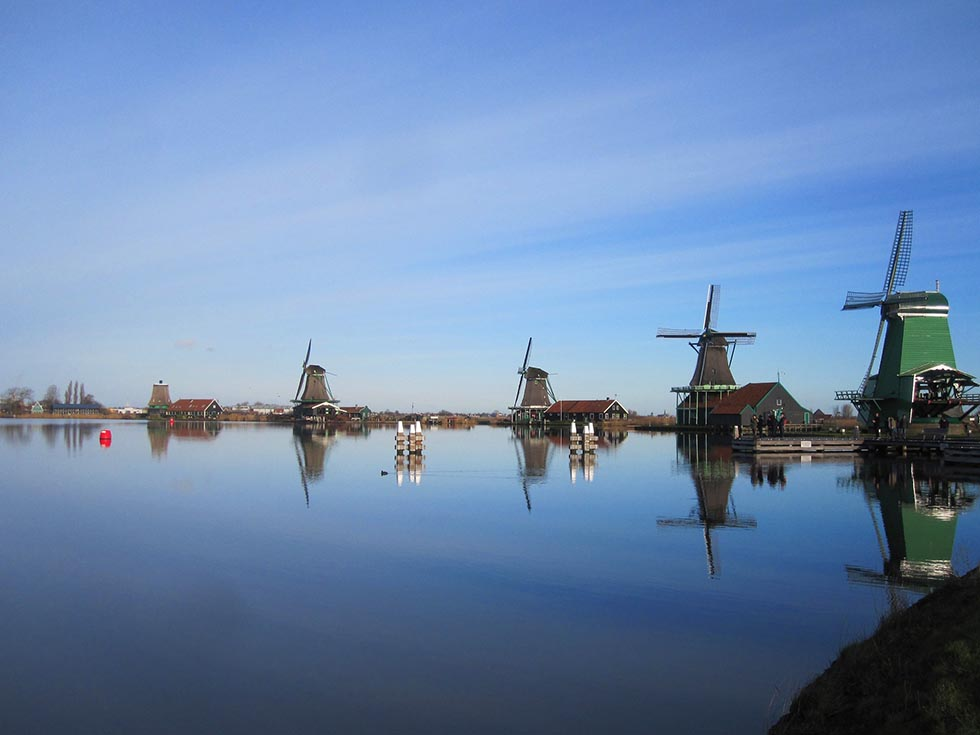 Four windmills at the waterfront in Zaanse Schans and the sky is fairly clear.