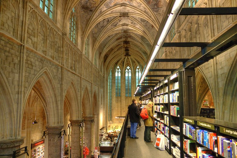 Two people reading inside a bookstore in a church in Maastricht.