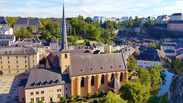 Yellow church and buildings in Luxembourg city seen from above.