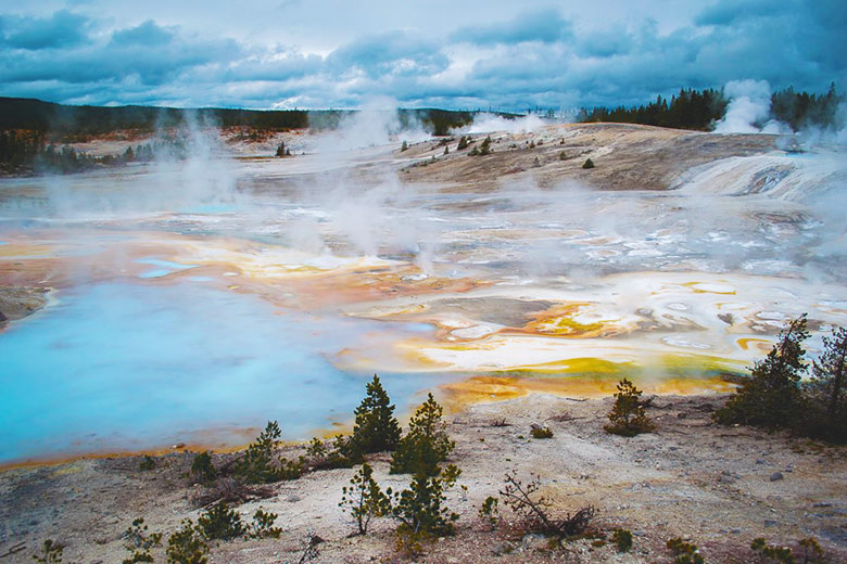 Steam above blue and yellow water at the Yellowstone National Park in the winter