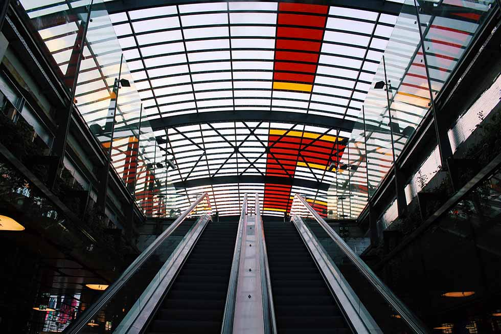 Escalator under a ceiling made of red and transparent glass at the central station Amsterdam. #photospots #Amsterdam #TheNetherlands #Holland #cities #europe #dutch #travel #bicycles #interiors #Beautiful #architecture #inspiration #picture #photography