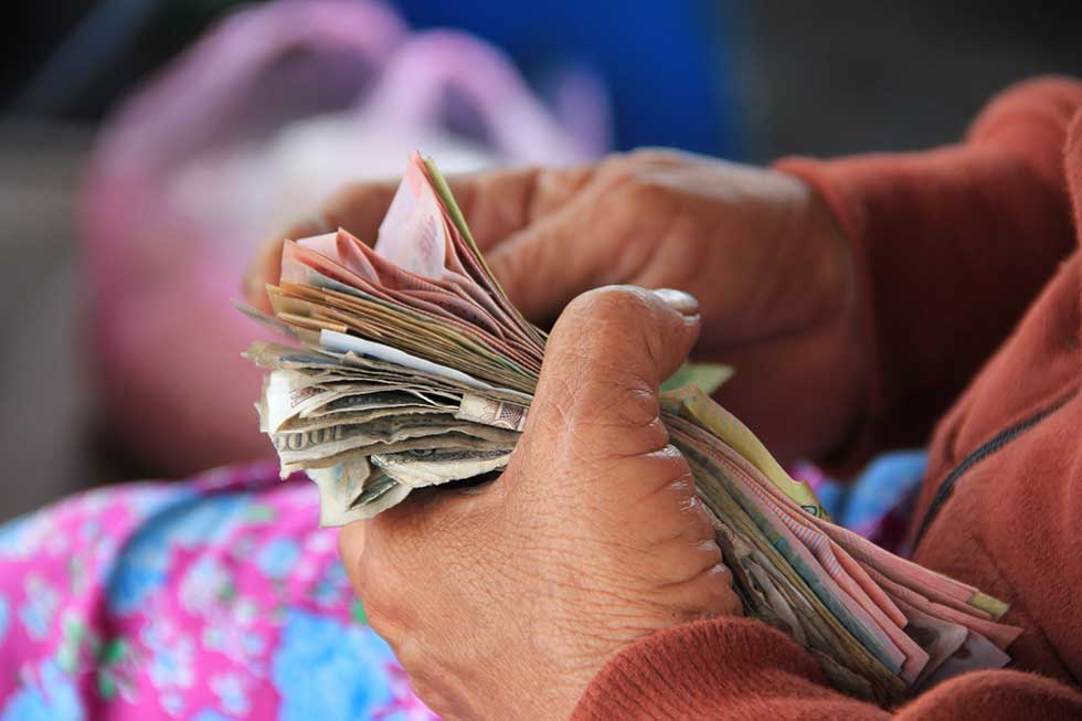 Hands of a person of color counting a lot of money #Travel #Scams
