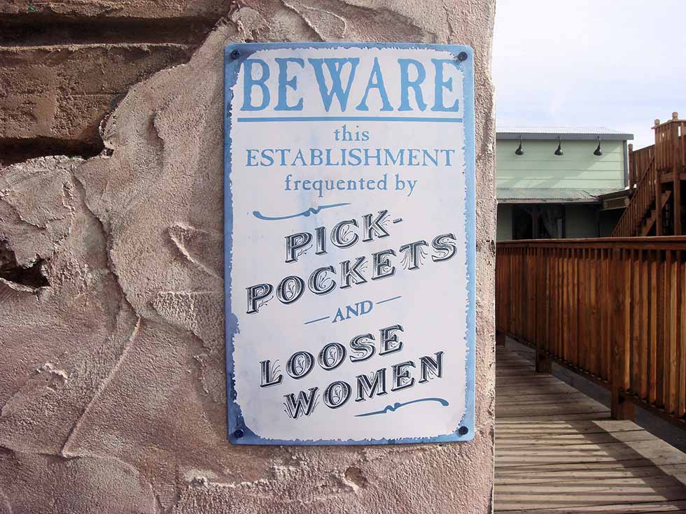 White board with blue letters warning about pick pockets and loose women outside a bar. #Travel #Scams