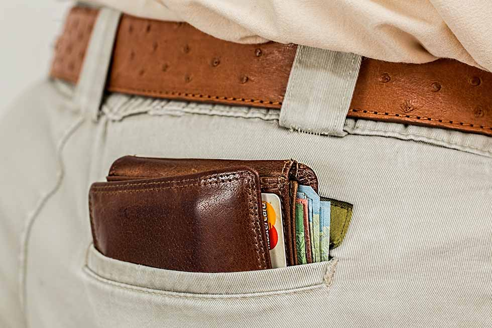 Brown leather wallet with cards and money in the back pocket of a male pair of paints. #Travel #Scams