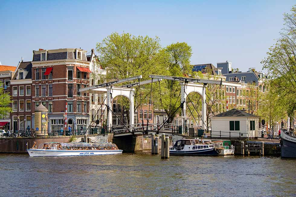 Bridge and boats at the Amstel River in Amsterdam. #photospots #Amsterdam #TheNetherlands #Holland #cities #europe #dutch #travel #bicycles #interiors #Beautiful #architecture #inspiration #picture #photography