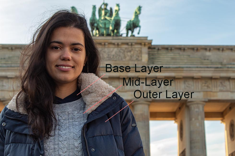 Brunette smiling in front of the Brandenburg Gate in Berlin.