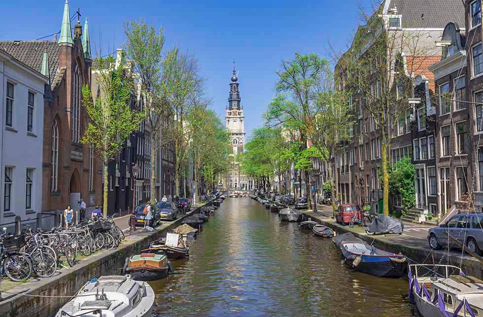 Houses and boats on both sides of a canal and the Zuiderkerk's tower in Amsterdam.