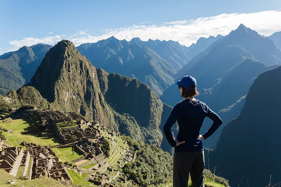 Woman wearing black clothes starring at Machu Picchu in Peru.