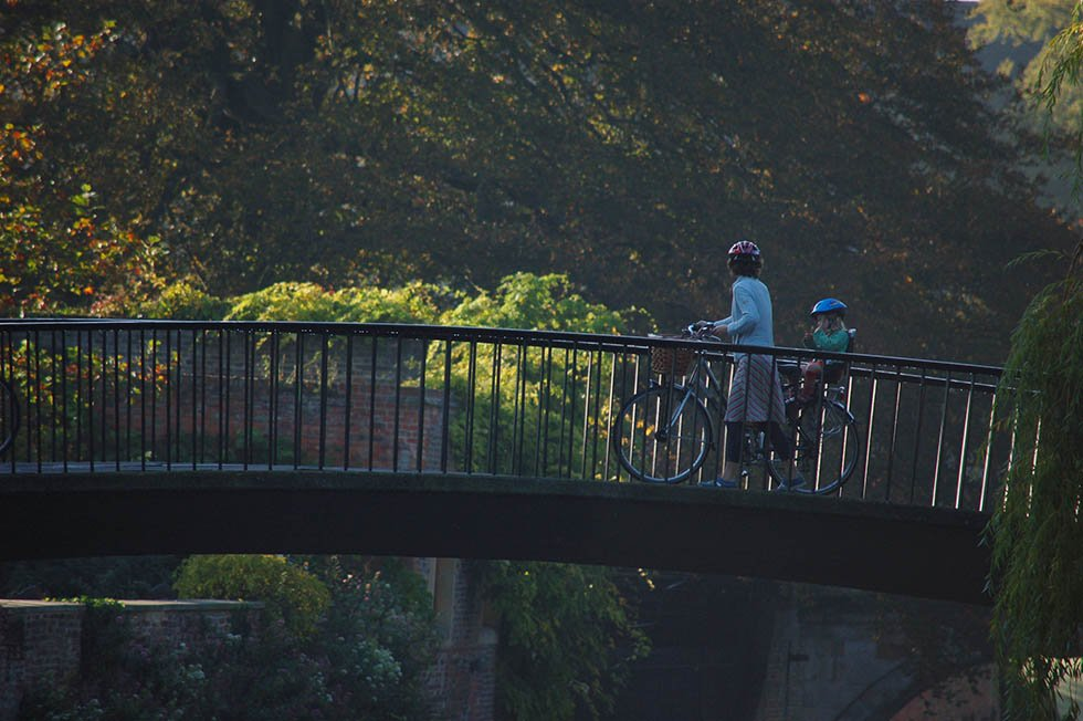 Mom and daughter crossing a bridge by bike in Cambridge