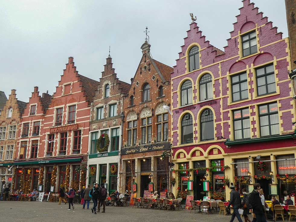 Pink and orange houses next to each other in the market in Bruges, Belgium