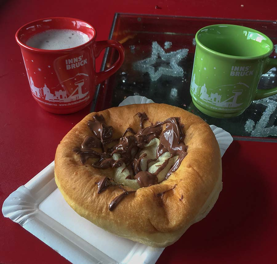 Chocolate on a piece of dough and two mugs on a red table in Innsbruck