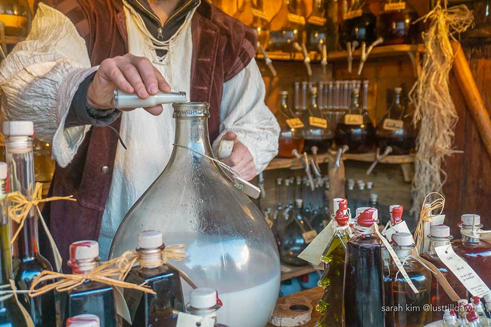 Man preparing white drink in traditional clothes in a Christmas market in Munich