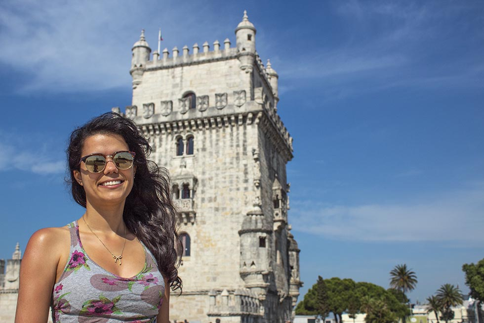 Brunette smiling at the camera in front of Belem Tower in Lisbon #Portugal #Europe #Travel