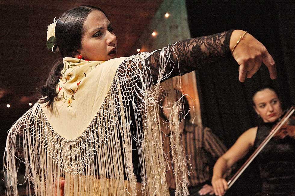 Woman dancing flamenco in a fairly illuminated room