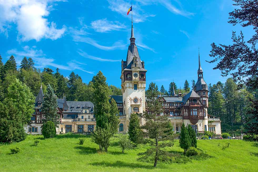 Green grass in front of the Peles Castle in Romania in a sunny day.