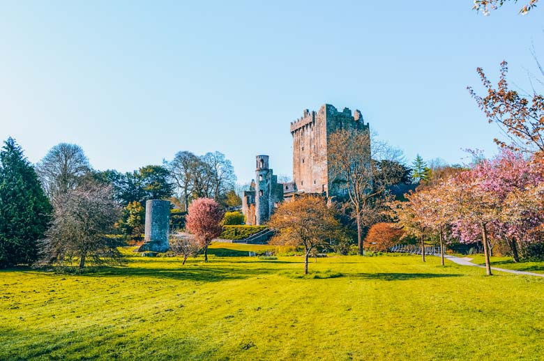 Blarney Castle in front of a green grass field with trees on a sunny day - a great day tour from Dublin!