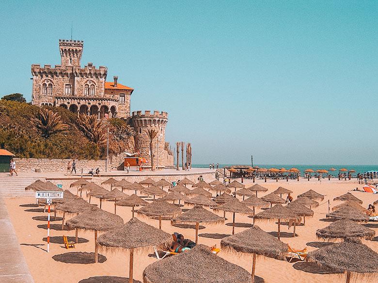 Castle near sun umbrellas at Tamariz beach in Estoril, Lisbon, Portugal