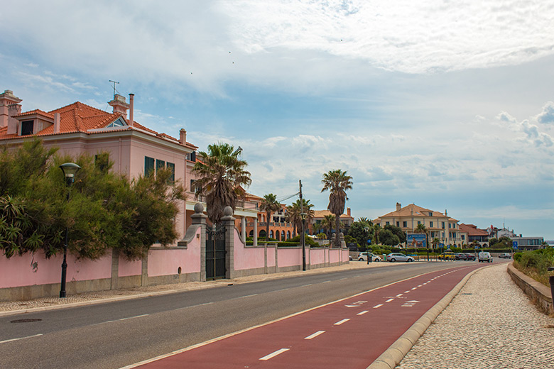 Bike path next to the street in Cascais in front of a pink house