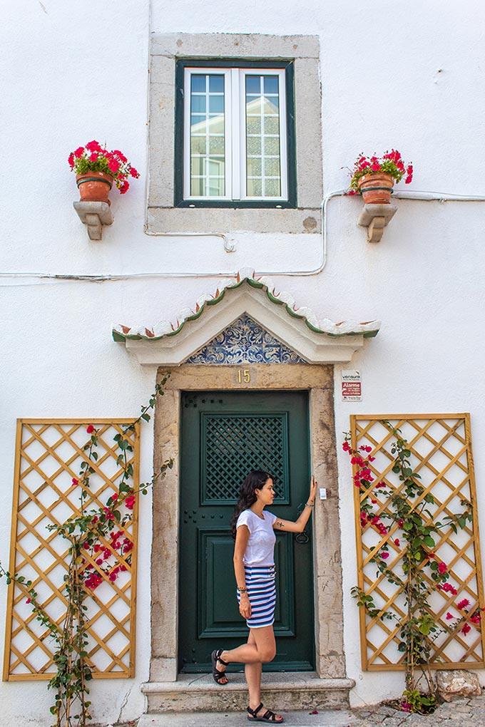 Woman standing in front of a green door staring away from the camera
