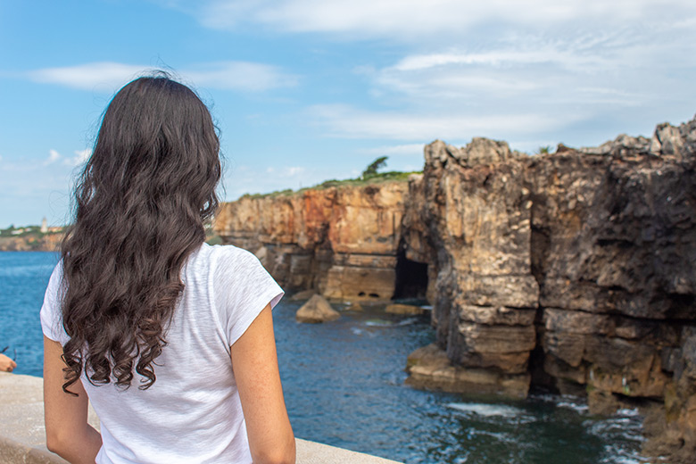 Brunette staring at the cliffs in Cascais, Portugal