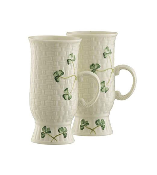 Two white belleek mugs decorated with green shamrocks
