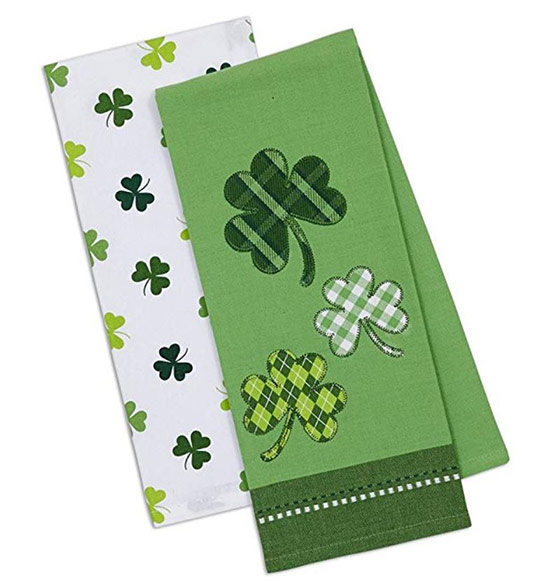 Folded white dish towel with green shamrocks and green dish towel