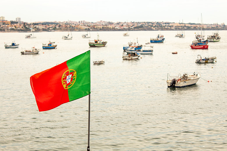 Portuguese flag near the water full with small boats in Cascais