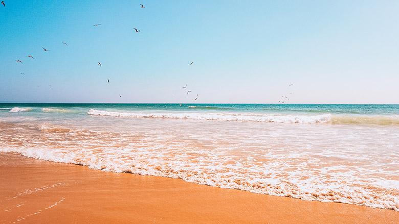 Orange sand and blue water in a sunny day at Praia da Mata in Lisbon, Portugal