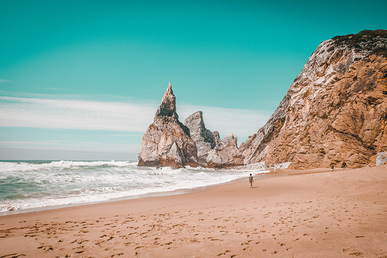 Person walking on the sand near rocks at Ursa beach in Lisbon, Portugal